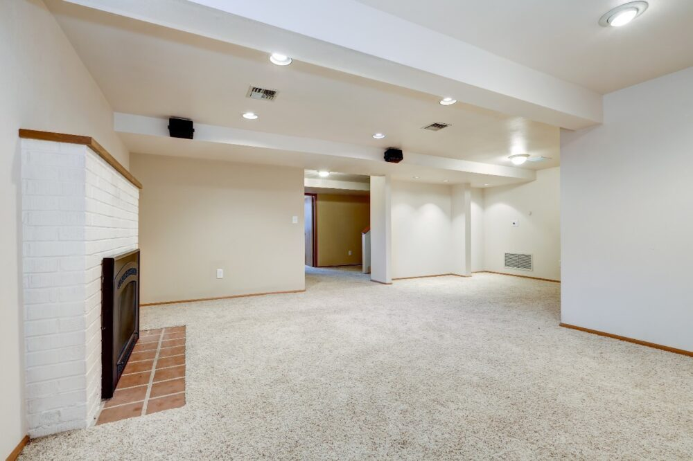 A finished basement ceiling with painted beams