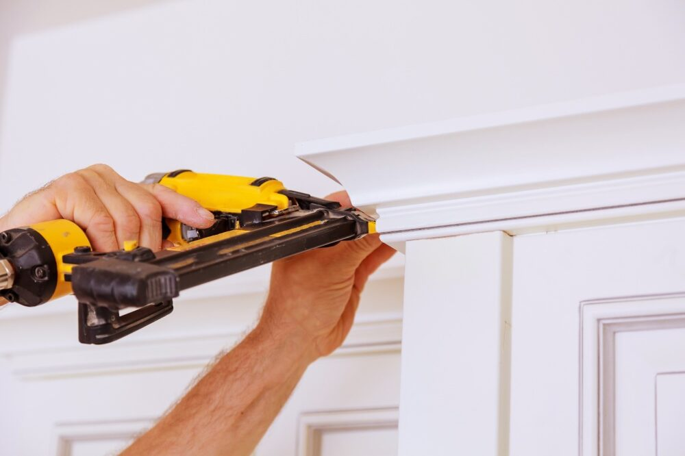 Man installing crown moulding on top of a cabinet