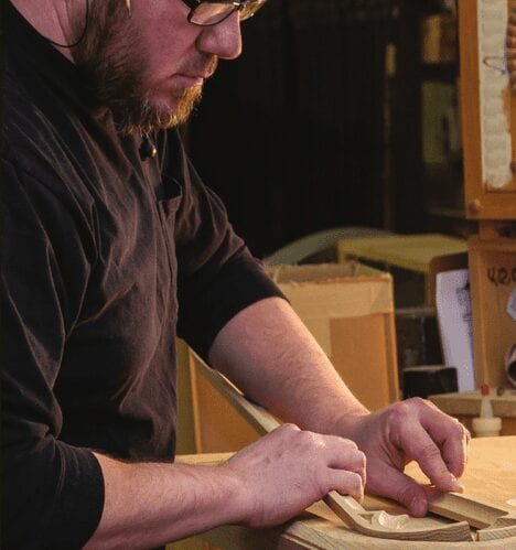 employee working on sanding wooden pieces