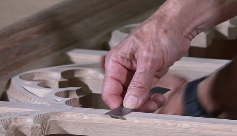 close up of hand measuring wood carving