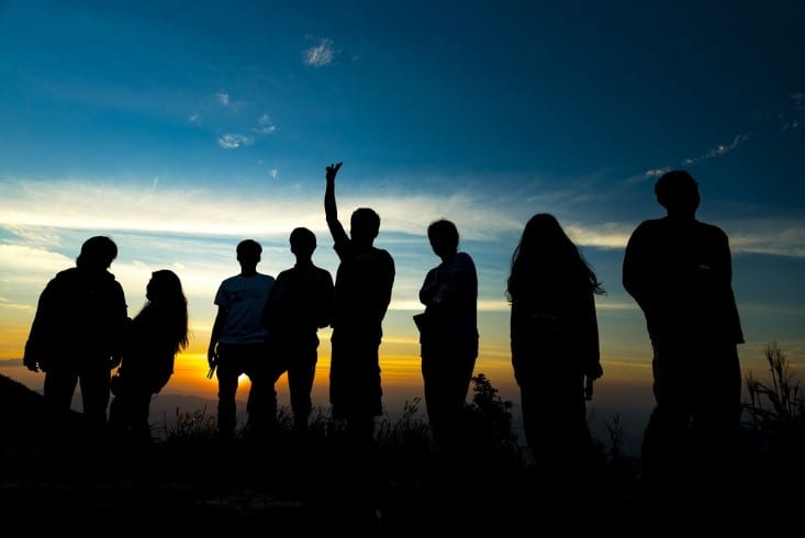 Youth group gathered outdoors at sunset for praise and worship