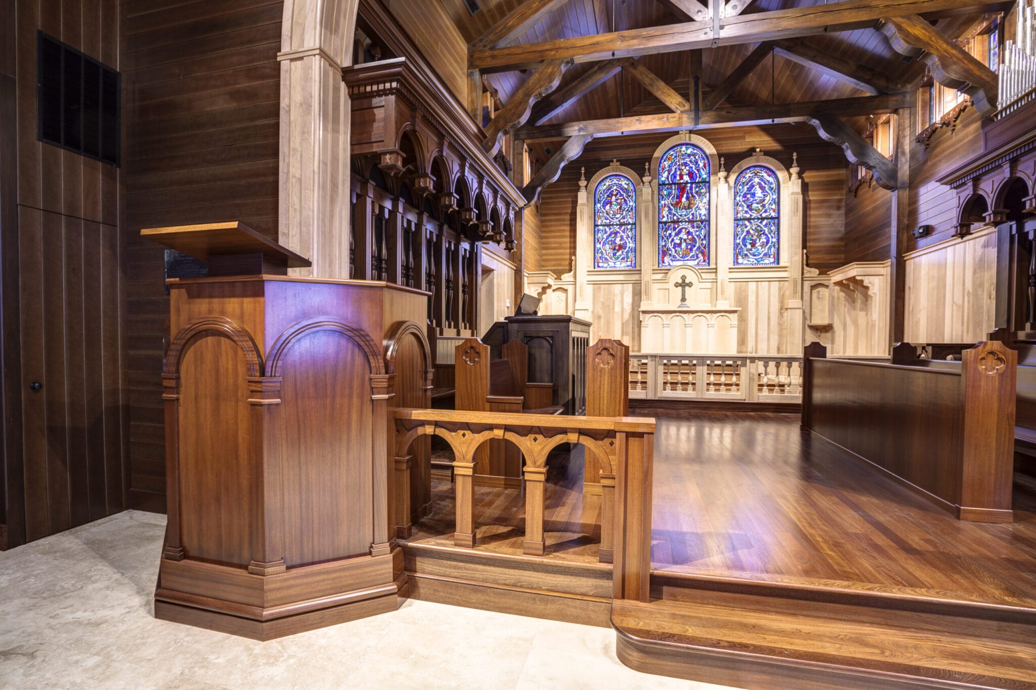 A wooden pulpit and beautiful wood church furniture with stained glass in the background at the Christ of the Redeemer Church in Longport, New Jersey.