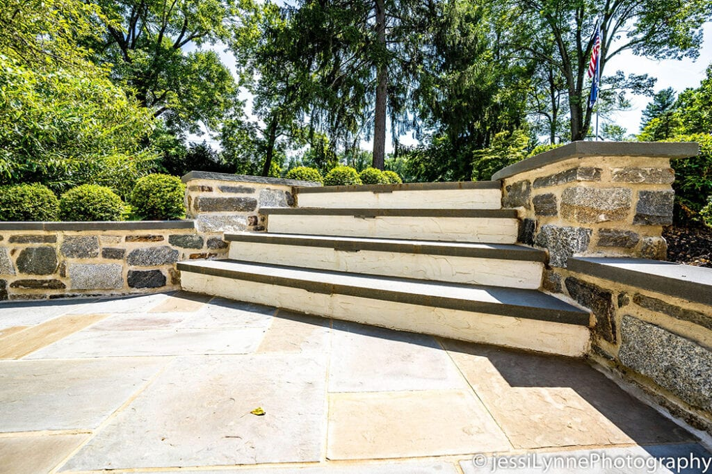 stone floored deck with stairs to yard
