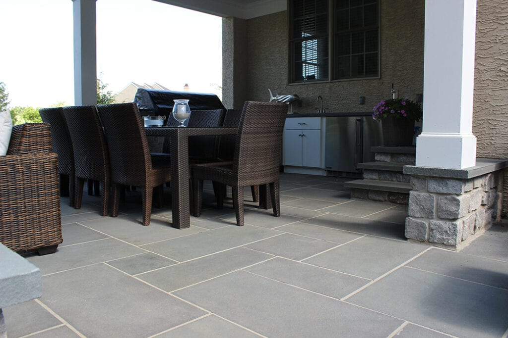 Gray stone patio with chairs and outdoor seating