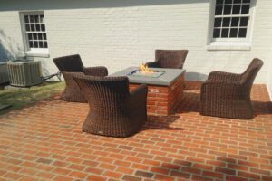 A brick fire pit seamlessly matches the brick patio it's on with wicker chairs surrounding it.
