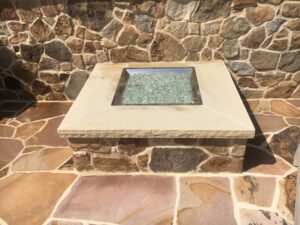 A fire table on irregular Tennessee stone provides a place for food and drinks.