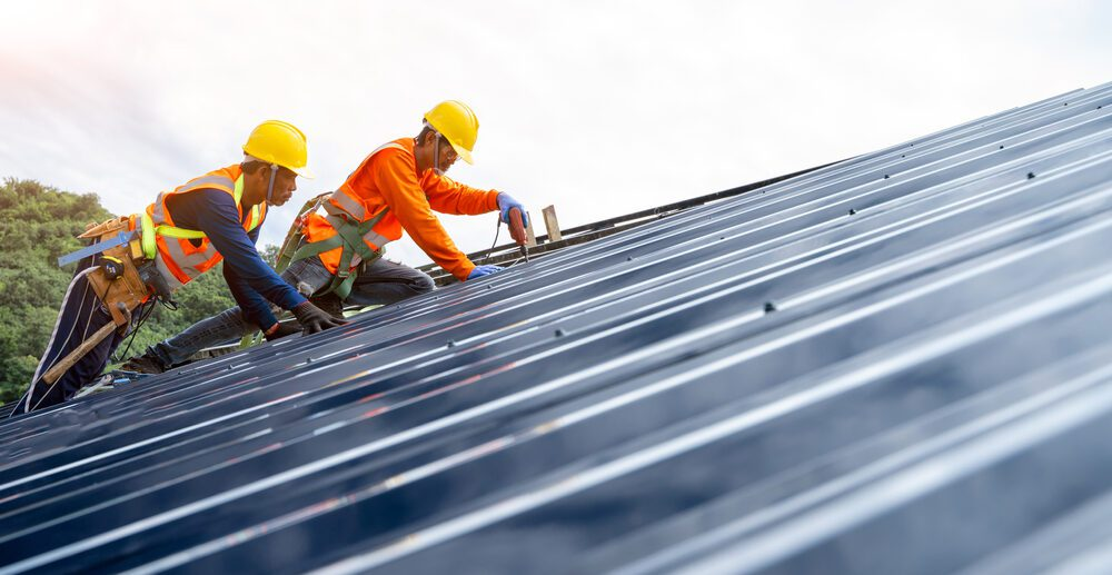 Two roofing technicians repair a commercial metal roof