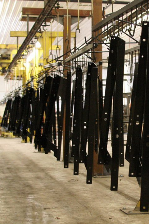 black coated parts hanging to dry