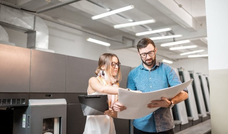 Employees review printed materials for a project