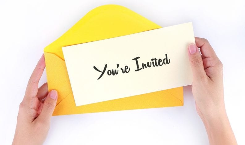 Hands holding an event invitation just received in an envelope
