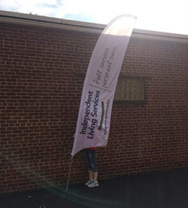 A woman places a temporary flag sign in front of a brick building
