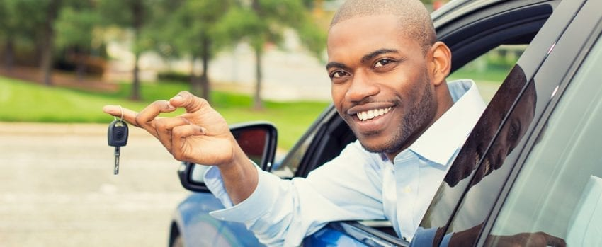 man holding key in new car