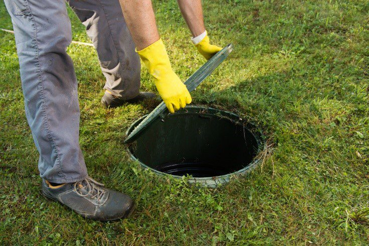 Homeowner opening septic tank before septic system maintenance pro's arrival