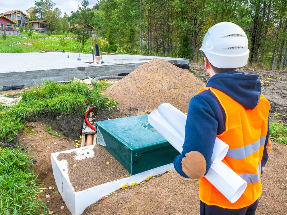 image of septic professional from behind in hi-vis vest and hardhat