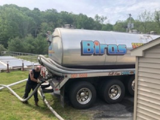 A Biros Septic truck is at a residential location for septic maintenance services.