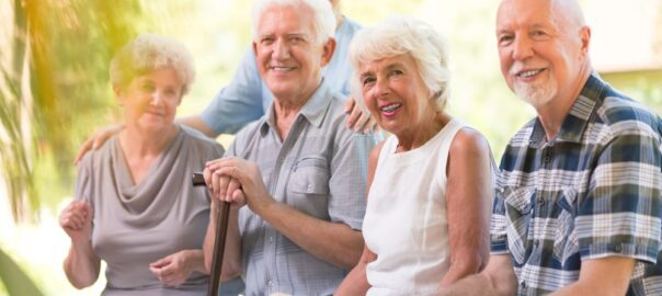 Smiling older adults spending time together at the patio of nursing house