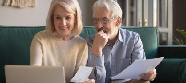 An older couple sits on a couch and evaluates their budget to prepare for life in a retirement community