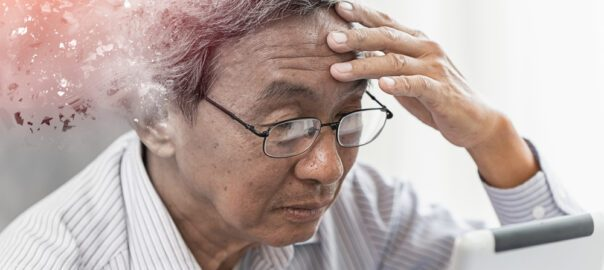 An Asian man holding his head, looking confused.