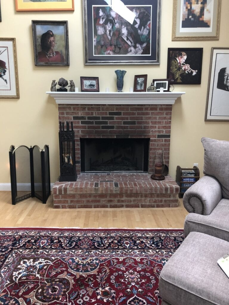 fireplace surrounded by framed art
