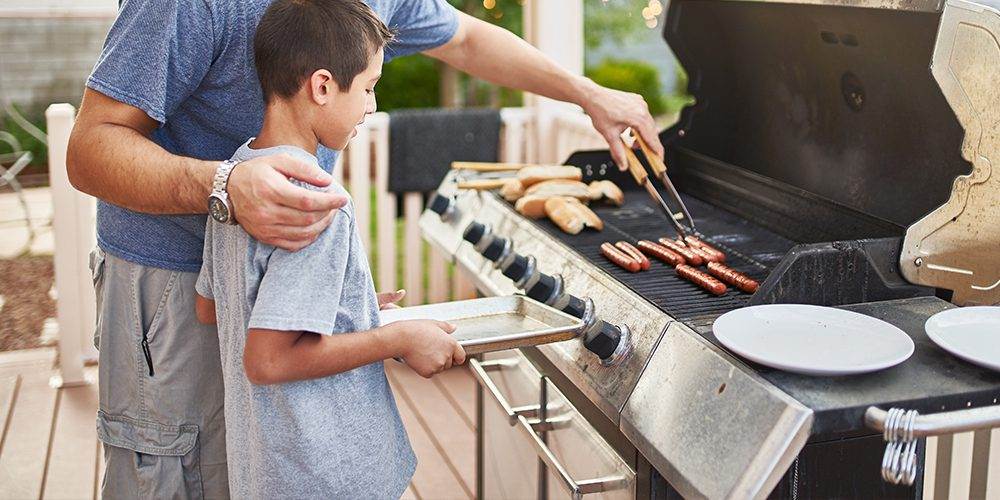 boy getting hotdog off grill