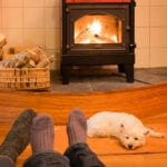 Socks and feet of a couple relaxing by fire with west highland terrier.