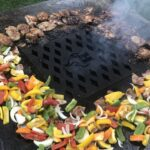 Chopped vegetables and chicken grilling on a Hancock Grill