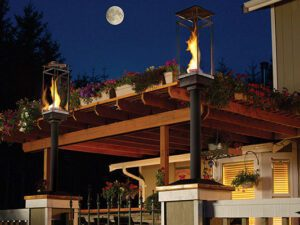 The flames inside two Tempest Torches dance on an outdoor patio.