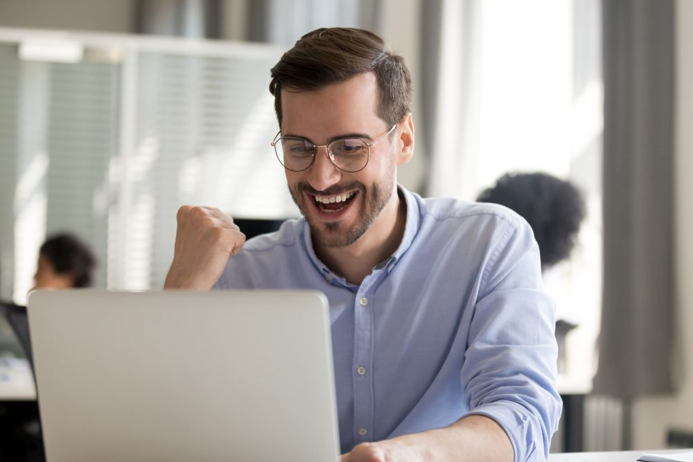 A happy man looking at his laptop in a business environment is excited his data was recovered successfully