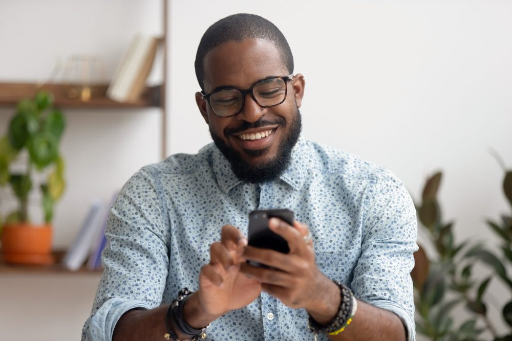 A businessman uses his cell phone with VoIP to answer business calls while working from home.