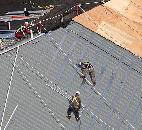 Men building roof together aerial shot