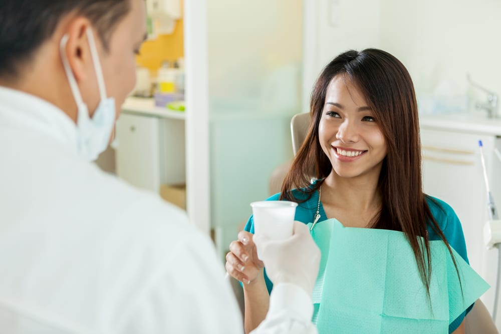 A smiling Asian woman takes a cup of water from her dentist to treat her dry mouth
