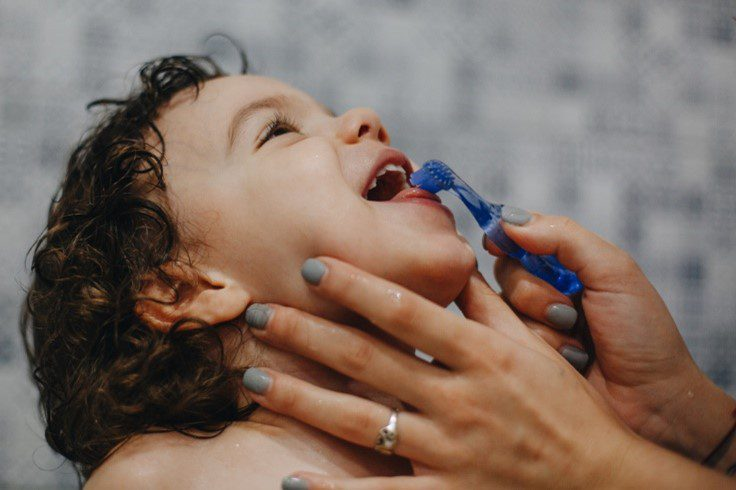 A child leans his head back while his mom brushes his teeth.