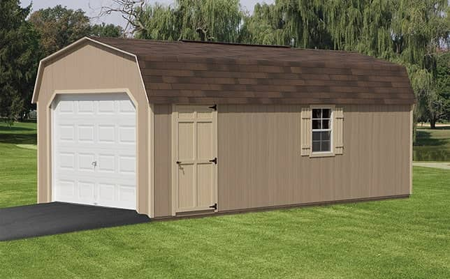 A brown mini-barn with a white garage door sits in a yard.