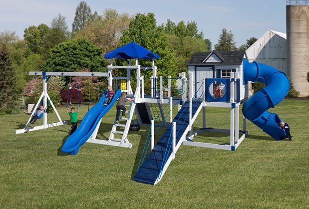 Children playing on a white and blue swing set.