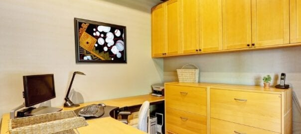 Uncluttered home office with light wood custom cabinetry