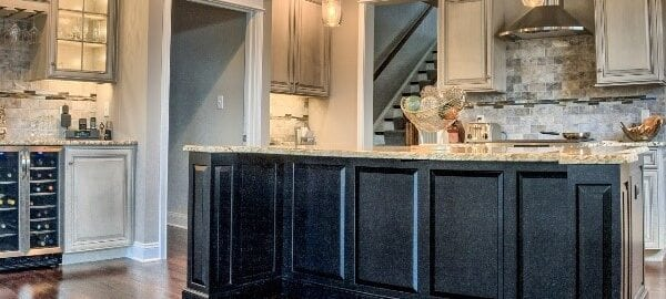 Dark kitchen island cabinetry in a modern kitchen by Red Rose Cabinetry