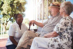 Retired couple chatting with caregiver at their personal care home