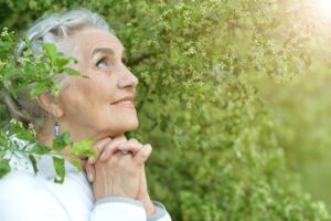 Senior woman praying in front of a background of green leaves