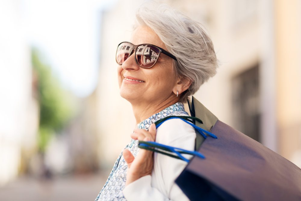 Older woman wearing sunglasses smiles with shopping bags over her shoulder.
