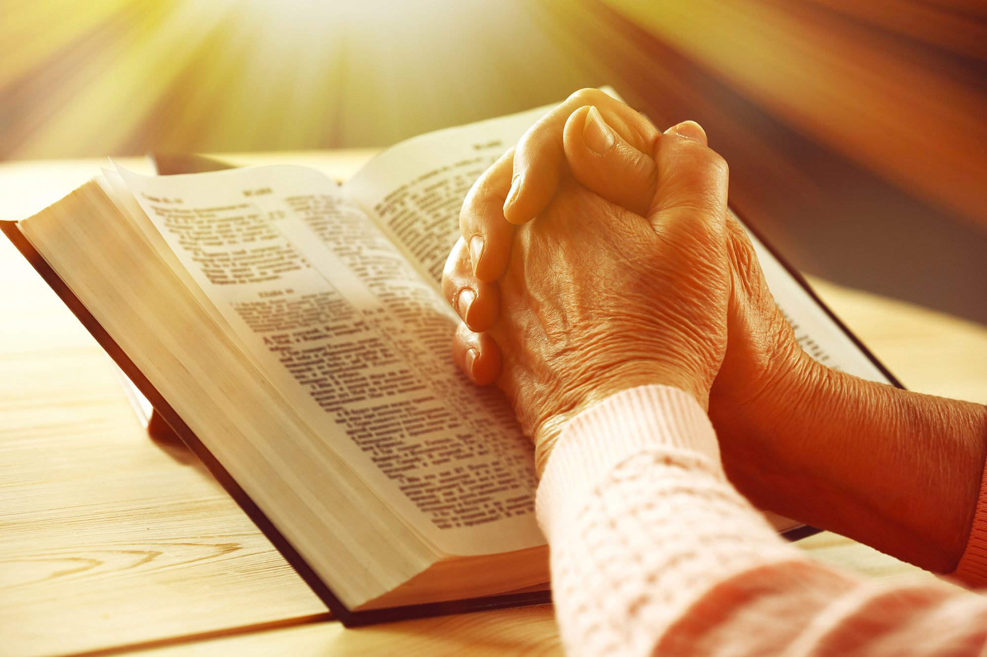 Clasped hands over a Bible indicate this person is praying.