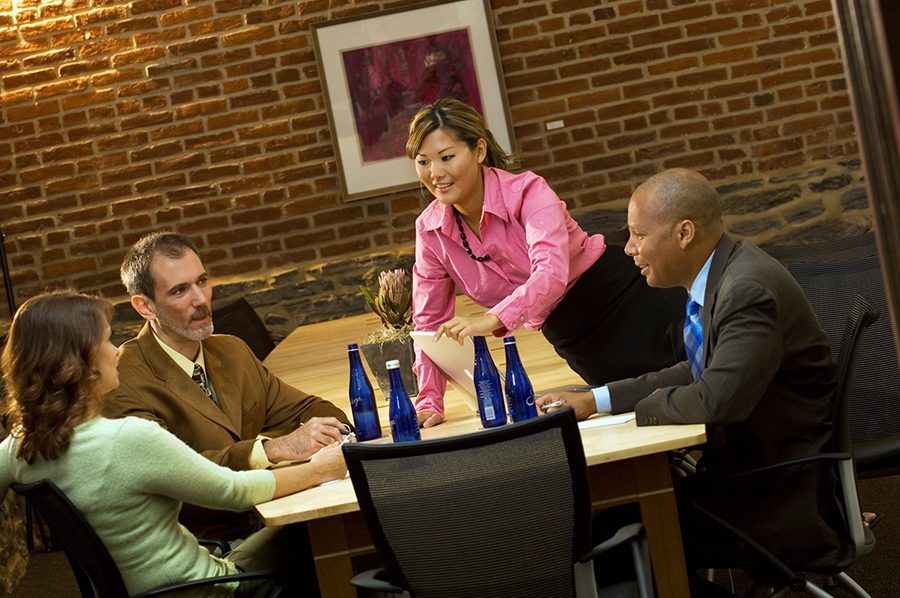 woman serving water to business meeting atendees