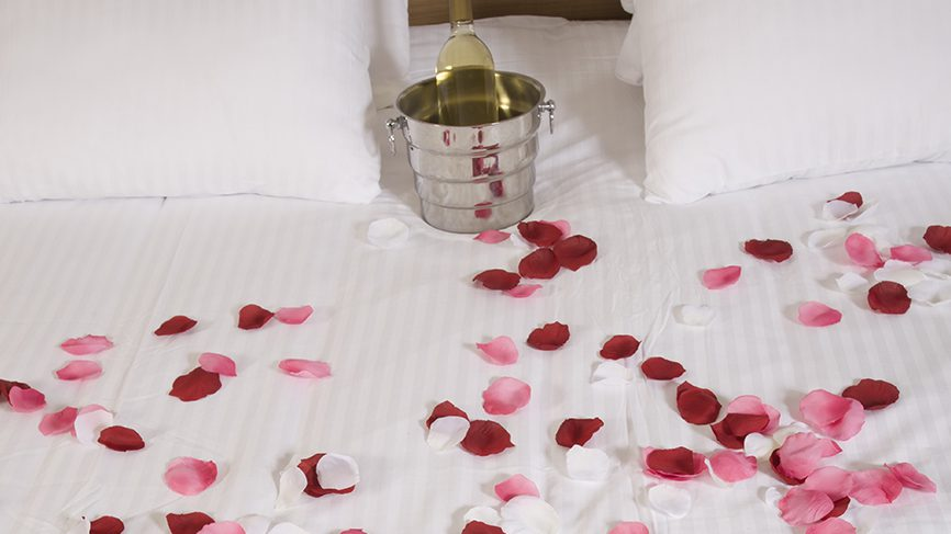 rose petals on bed with bucket of wine