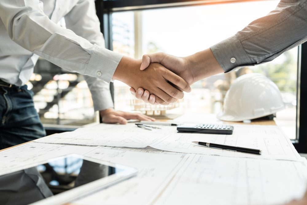 two men in an office shaking hands over contractor agreement