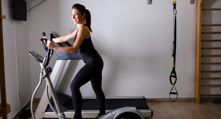 Woman using an elliptical in her home gym