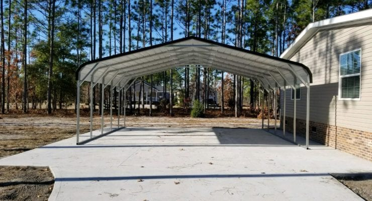 A double-wide metal carport sits on a concrete slab next to a beige home with blue skies and tall trees in the background
