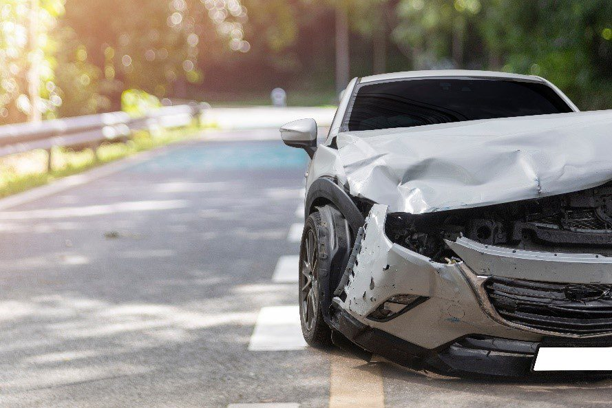 Wrecked car along the side of the road following a hit and run.