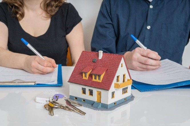 Two people signing paperwork to become tenants in common on home purchase
