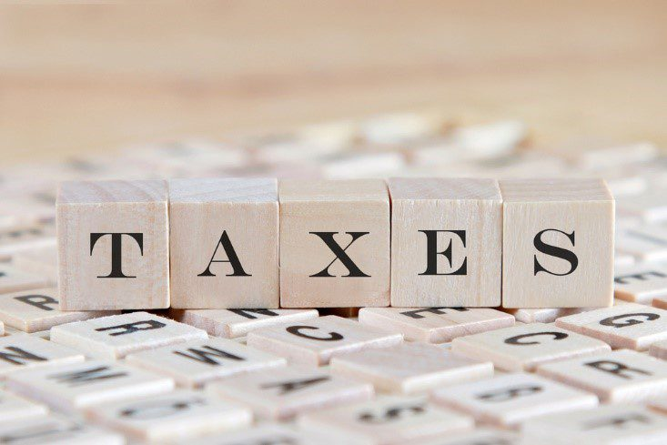 Concept image with the word TAXES spelled out in wooden blocks