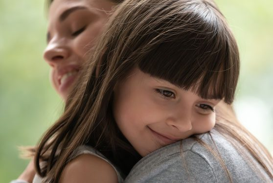 Side view close up head shot happy little adopted kid girl put head on mothers shoulder, feeling love and support. Small cute daughter hugging embracing cuddling young smiling mother at new home.