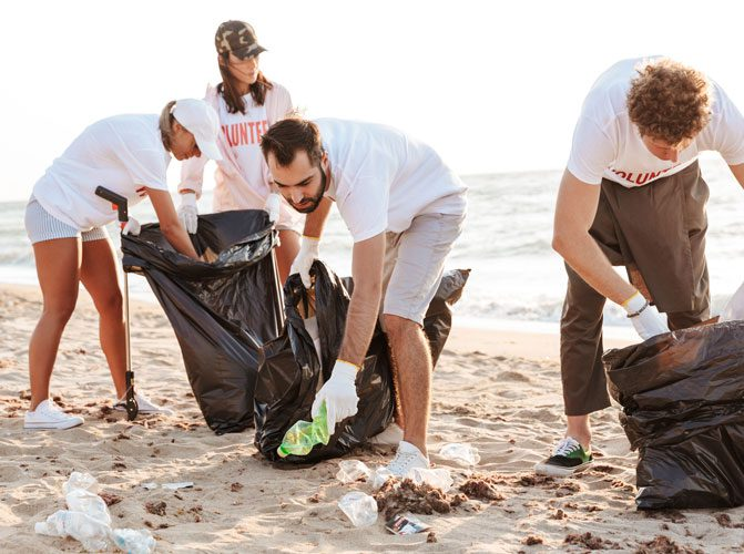 Photo of caucasian eco volunteers people cleaning beach from plastic with trash bags at seaside